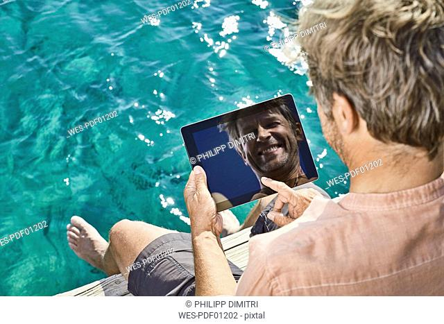 Smiling man sitting on jetty looking at tablet