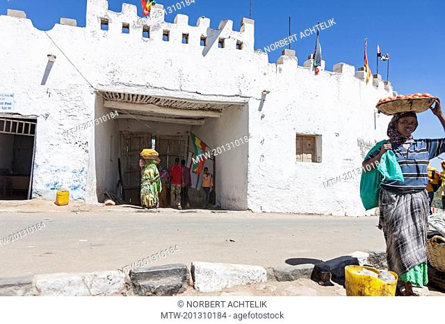 Vendors carrying baskets on head while boys standing by whitewashed structure