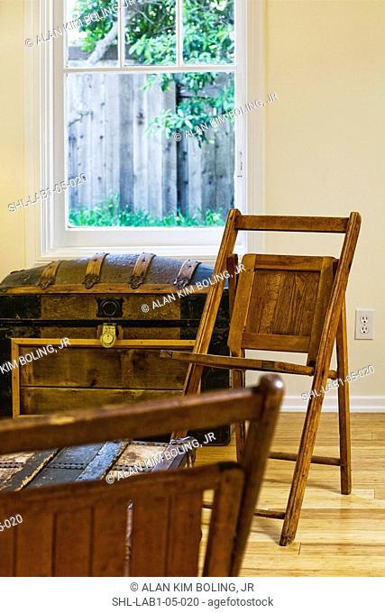 Brown wooden folding chairs and old storage trunk