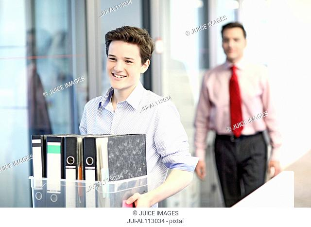Teenage boy carrying files in office