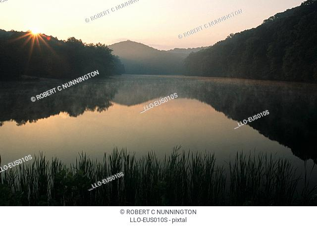 Scenic View of Sunrise Over Lake with Mountains Reflected in the Water  Lake Brown, Indiana State, United States of America