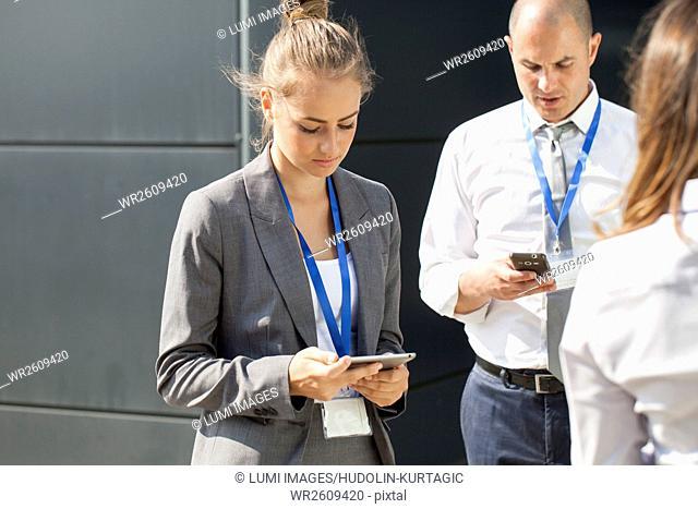 Business people looking at smartphones
