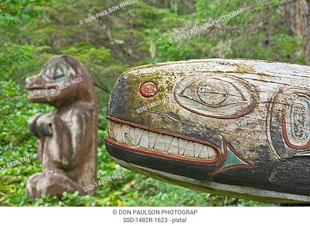 Totem poles of a killer whale and a black bear in a forest, Kasaan Totem Park, Tongass National Forest, Alaska, USA
