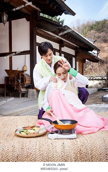 Loving husband giving a massage to his wife cooking
