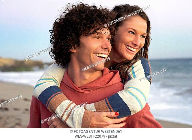Happy young man carrying girlfriend piggyback on the beach