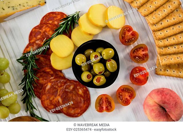 Variety of cheese with grapes, olives, salami, and crackers