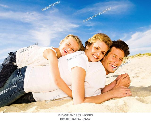 Caucasian family laying in pile on beach