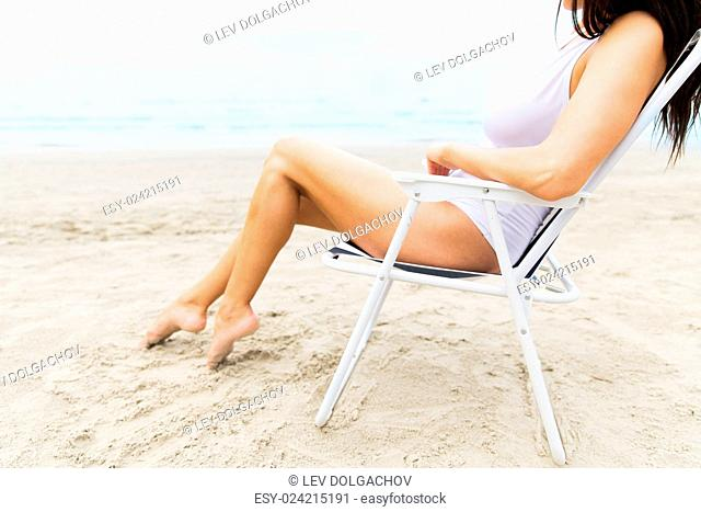 summer vacation, tourism, travel, holidays and people concept - close up of young woman sunbathing in lounge or folding chair on beach