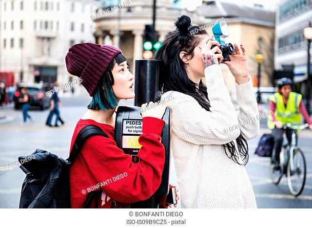 Two young stylish women taking photographs on street, London, UK