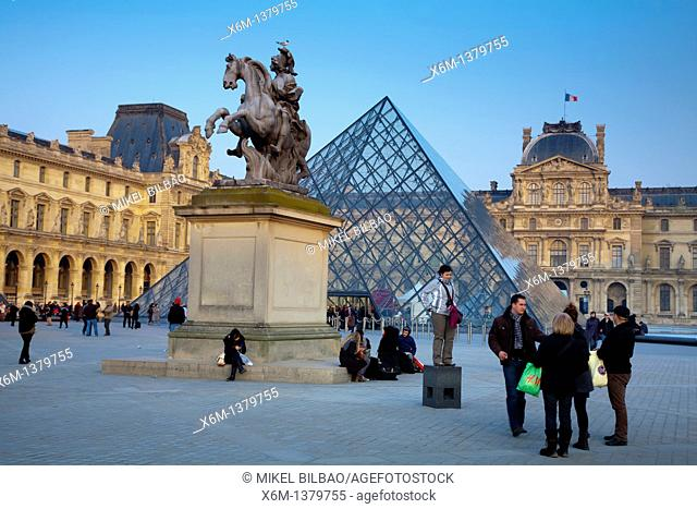 Louis XIV statue Sun King and Crystal Piramid in front of the Louvre Museum  Paris, France