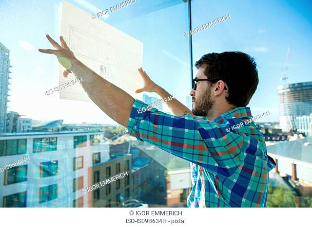 Man, standing beside office window, holding plans up to window