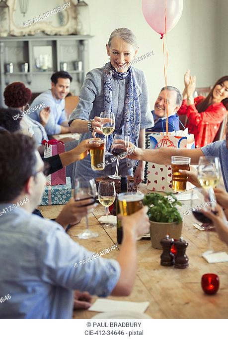 Friends toasting wine and beer glasses at restaurant birthday party