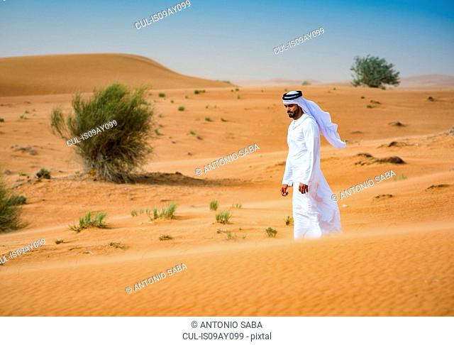 Middle eastern man wearing traditional clothes walking in desert, Dubai, United Arab Emirates