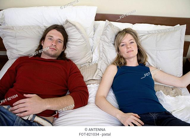 Portrait of a young couple lying down on a bed