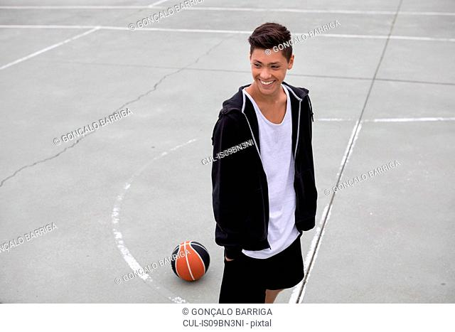 Male teenage basketball player on basketball court, smiling