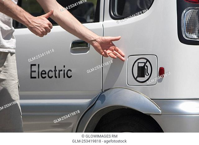 Man pointing at an electric car, Los Angeles, California, USA