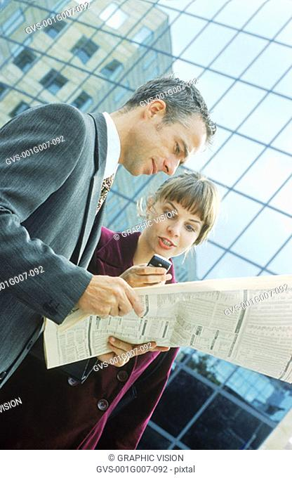 Young business executives reading the newspaper