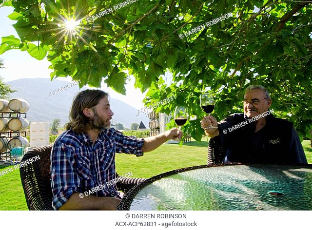 Winemakers raise a glass overlooking the vineyards of Eau Vivre winery in Keremeos in the Similkameen region of British Columbia, Canada
