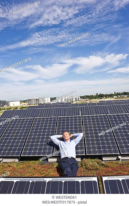 Germany, Munich, Mature man resting on panel in solar plant, smiling