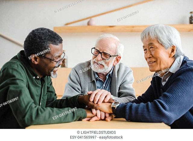 group of multiethnic senior friends making team gesture and smiling