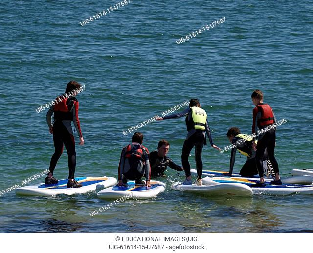 Children learning to stand on a stand up paddle-board, Swanpool, Falmouth, Cornwall, UK