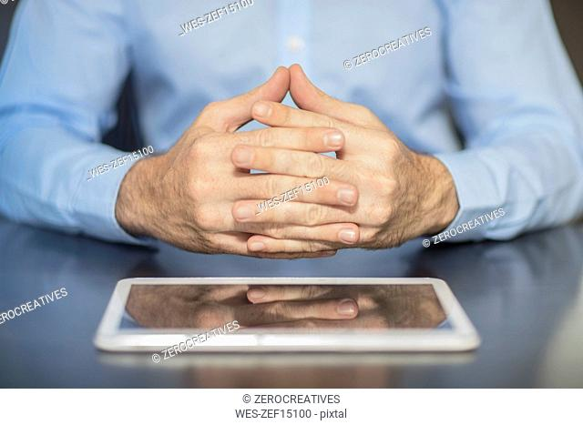 Man sitting at office desk with tablet folding hands