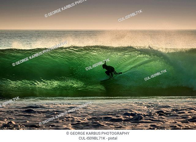 Surfer surfing on barreling wave, Crab Island, Doolin, Clare, Ireland