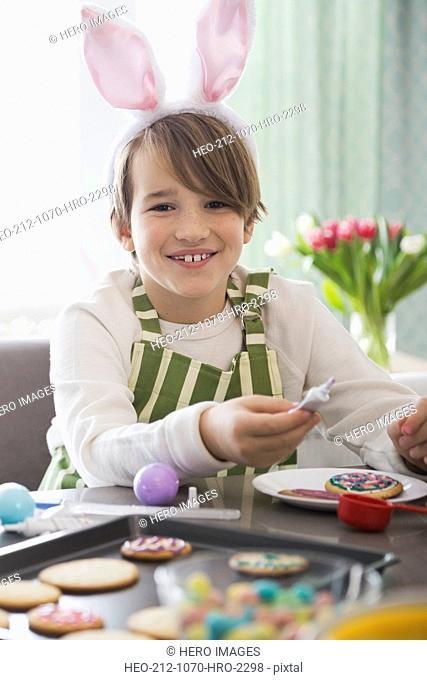 Portrait of boy wearing rabbit ears decorating Easter cookies