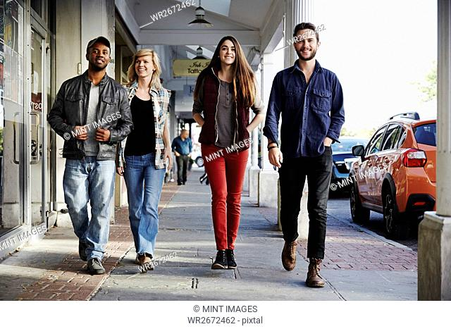Two young men and two young women walking along a sidewalk, smiling into shot