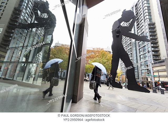 Seattle, Washington: Woman walks by the Hammering Man at the Seattle Art Museum as the first storm of the season lashes the city with high winds and rain