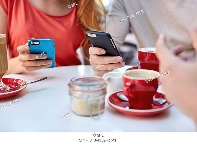 MODEL RELEASED. Young people in cafe using smartphones