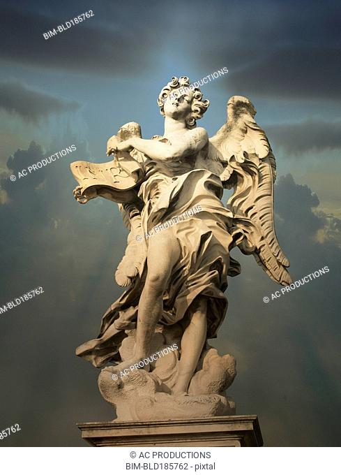 Low angle view of statue under cloudy sky