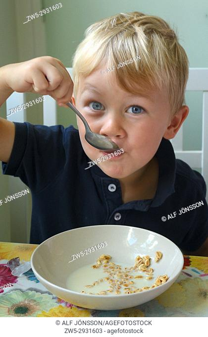 Little boy, four years old, have lunch with cereals with milk