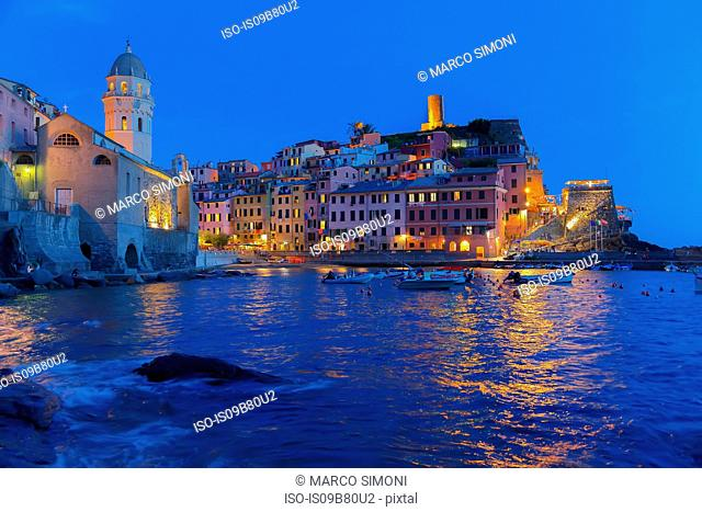 Cliff side fishing village illuminated at dusk, Vernazza, Liguria, Italy, Europe