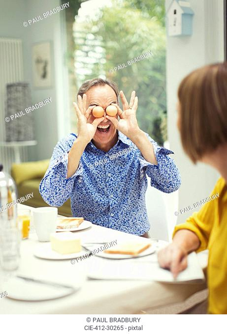Playful mature man covering eyes with eggs at breakfast table