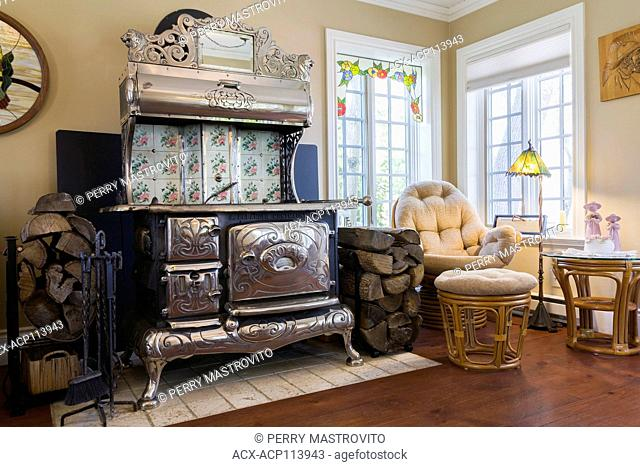 Antique black cast iron and chrome Royal wood burning cook stove in the family room inside an old reconstructed 1886 Canadiana cottage style residential home