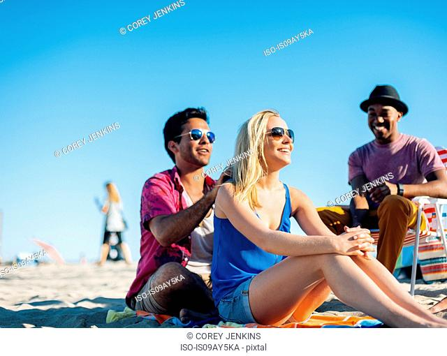 Young man applying suncream to friends shoulders on beach, Santa Monica, California, USA