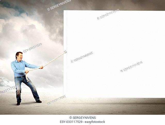 Adult man pulling blank banner. Place for text