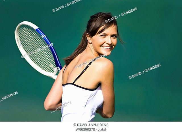 A happy tennis player smiles on court