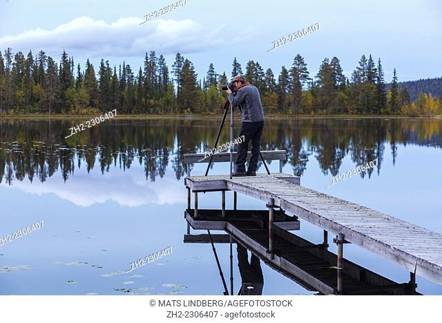 Photographer standing on a landing stage and taking photo in Gällivare, Swedish lapland