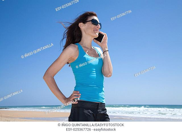 profile portrait of brunette woman with black sunglasses and blue cyan shirt smiling and talking on mobile phone smartphone at beach