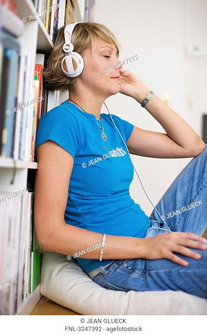 Young woman using headphones, side view
