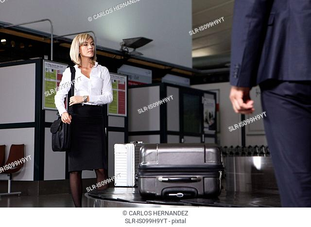 Mid adult businesswoman waiting for luggage in airport baggage re-claim