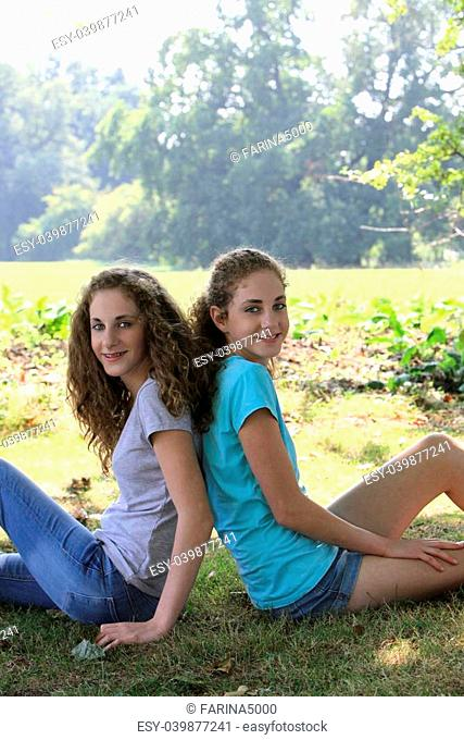 Two beautiful young girls in the park relaxing sitting back to back on the ground looking at the camera with friendly smiles
