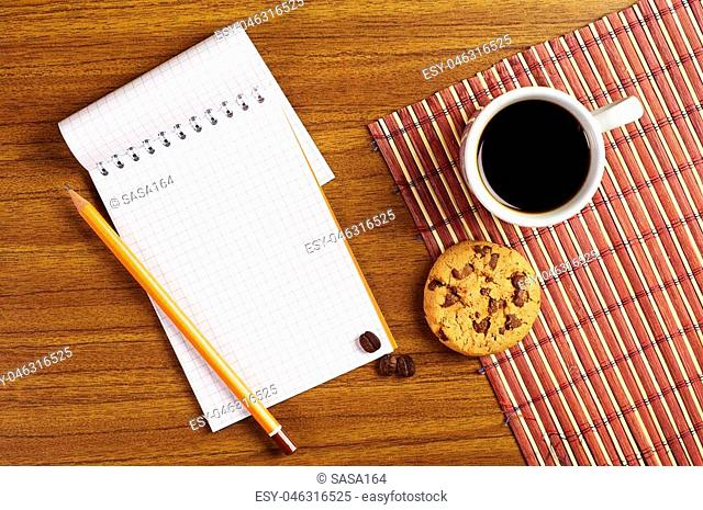 Opened notepad and cup of coffee with chocolate cookies on wooden table