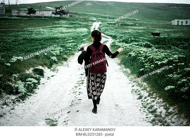 Caucasian woman walking on dirt road carrying wildflowers