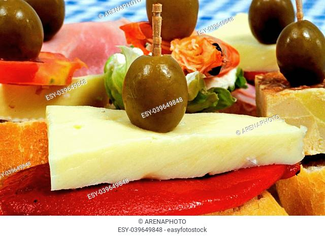 Spanish tapas selection, red pepper and cheese and topped with a green olive and served on crusty bread in the foreground, Andalusia, Spain, Western Europe