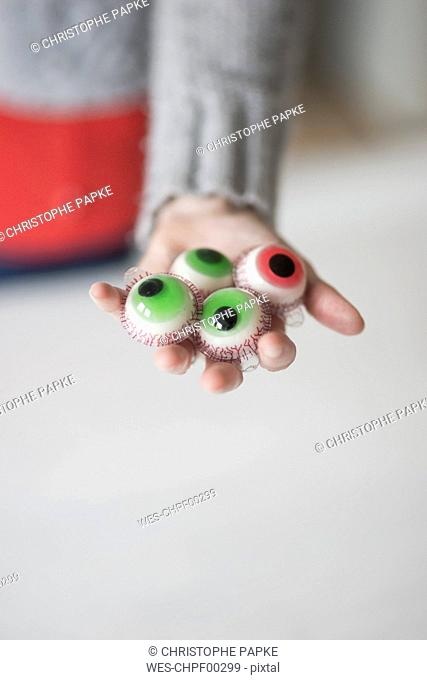Woman holding artificial sweets eyes