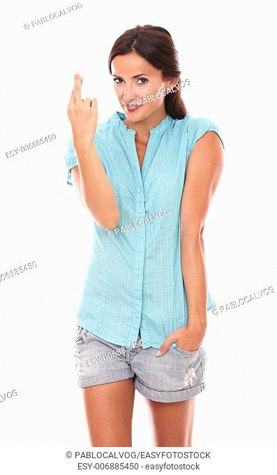 Smiling female with crossing fingers for luck sign while looking at you in white background