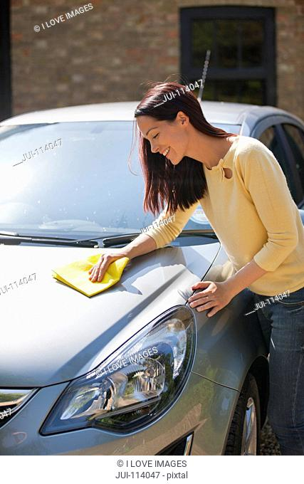 Woman washing and wiping car with cloth in sunny summer driveway